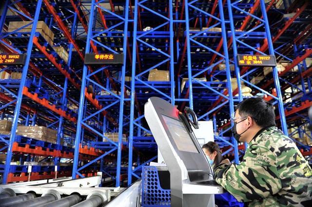 在江西一家工厂的生产线,操作员通过智能选料设备准备零部件。(李悭摄)