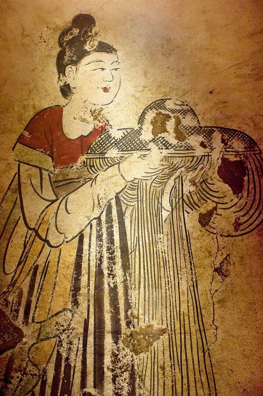 在陕西礼泉县昭陵发掘的燕德妃墓出土的《捧帷帽侍女图》壁画中,可见一位身穿半臂间色高腰条纹裙,头梳单螺高髻的侍女,捧着一件帷帽