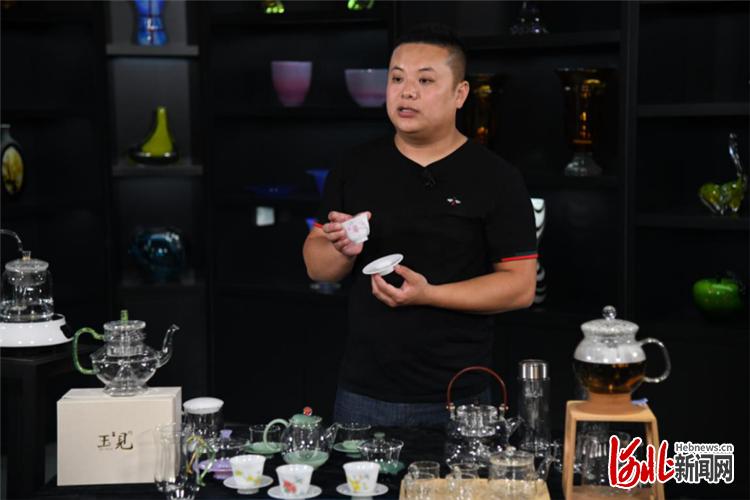 """永华汇玻璃制品有限公司的代表正在展示""""玉见""""品牌产品。"""