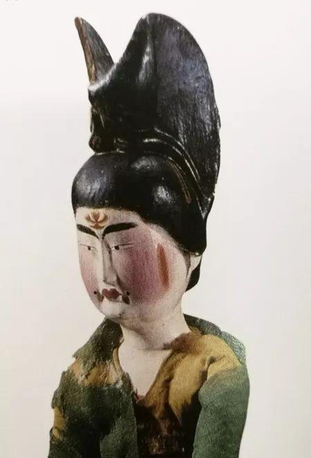 新疆吐鲁番市阿斯塔那206号墓出土,头梳高髻,饰花钿、斜红和面靥并点唇的女俑