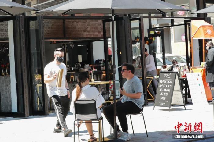 当地时间6月22日,纽约曼哈顿一家餐厅,顾客在户外用餐。当日,纽约市按预定计划进入第二阶段重启,市政府预计将有约30万人重返工作岗位。按照纽约州的重启规则,第二阶段重启中,零售店、理发店等商家满足条件可以开展室内经营。餐厅可以申请设置室外用餐区。商场、影剧院、健身房等依然保持关闭。中新社记者 廖攀 摄