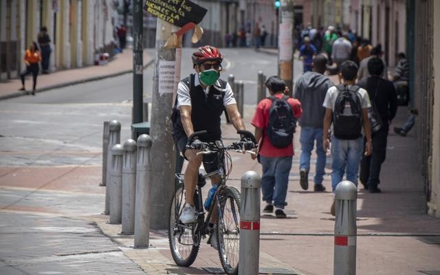 在厄瓜多尔首都基多街头,一名男子佩戴口罩骑行。新华社资料