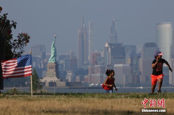 当地时间7月4日,两名孩童在纽约曼哈顿对岸的海滨草坪上奔跑。当日是美国独立日,美国多地疫情仍面临严峻形势。美国约翰斯·霍普金斯大学实时统计数据显示,美国累计新冠确诊病例4日已超过280万例。中新社记者 廖攀 摄