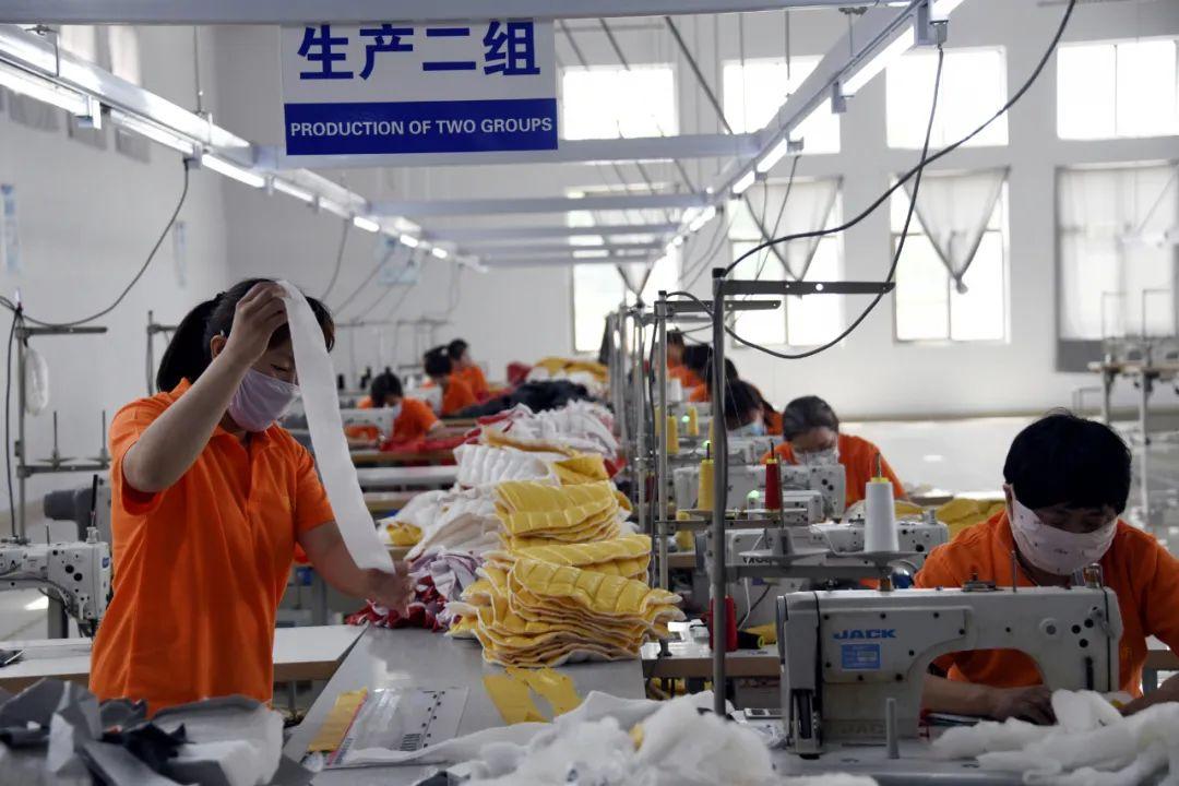 """山东某""""卫星工厂""""内,工人在加工羽绒服。这家羽绒服生产企业以总部为中心,建设3处""""卫星工厂"""",辐射带动周边经济"""