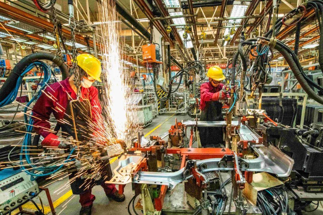 工人在山东省青州市一家汽车制造企业的冲焊车间内生产作业