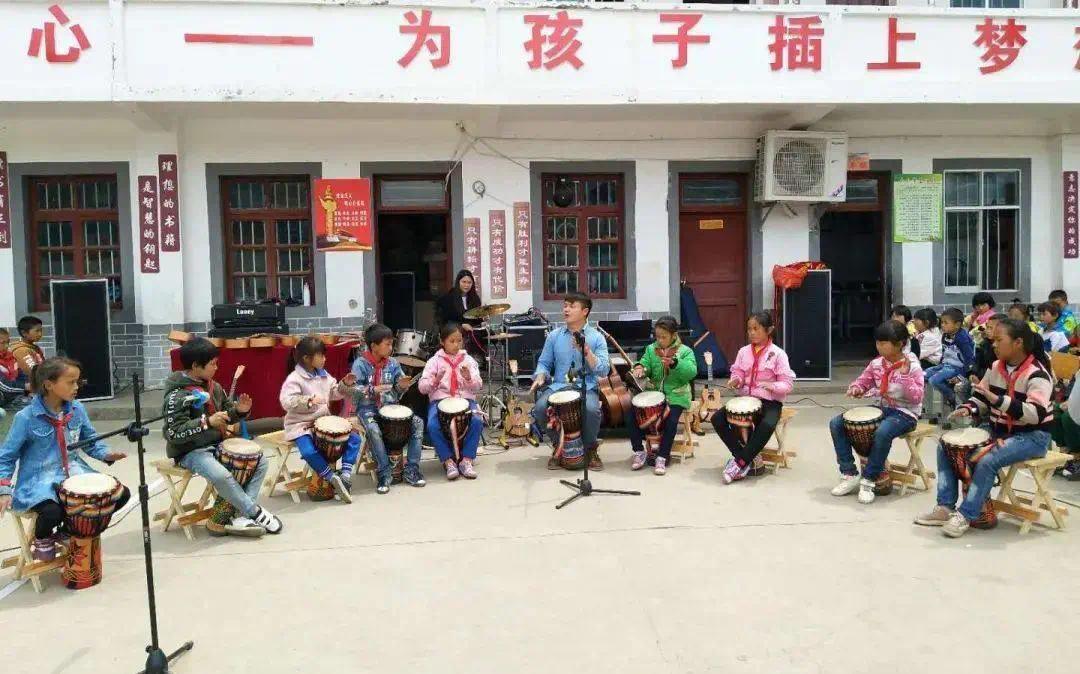 | 学校的操场上,学生们在学习手打鼓。