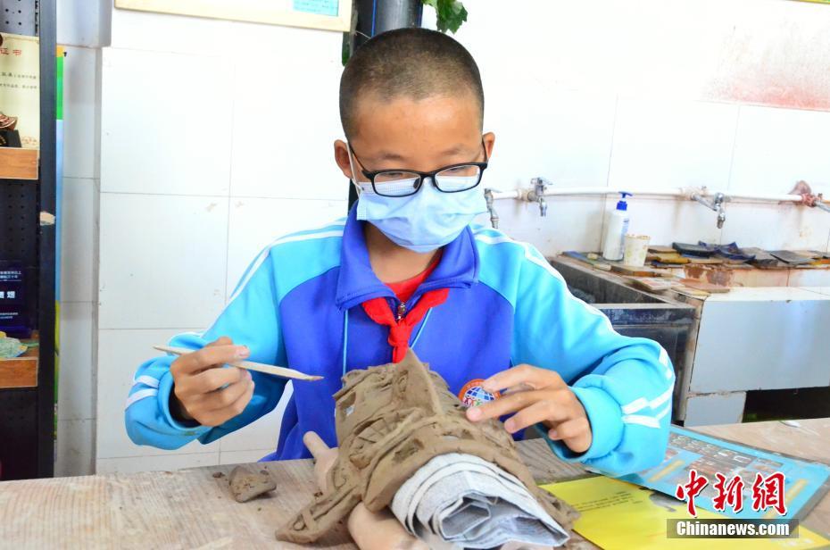 图为学生制作陶艺面具