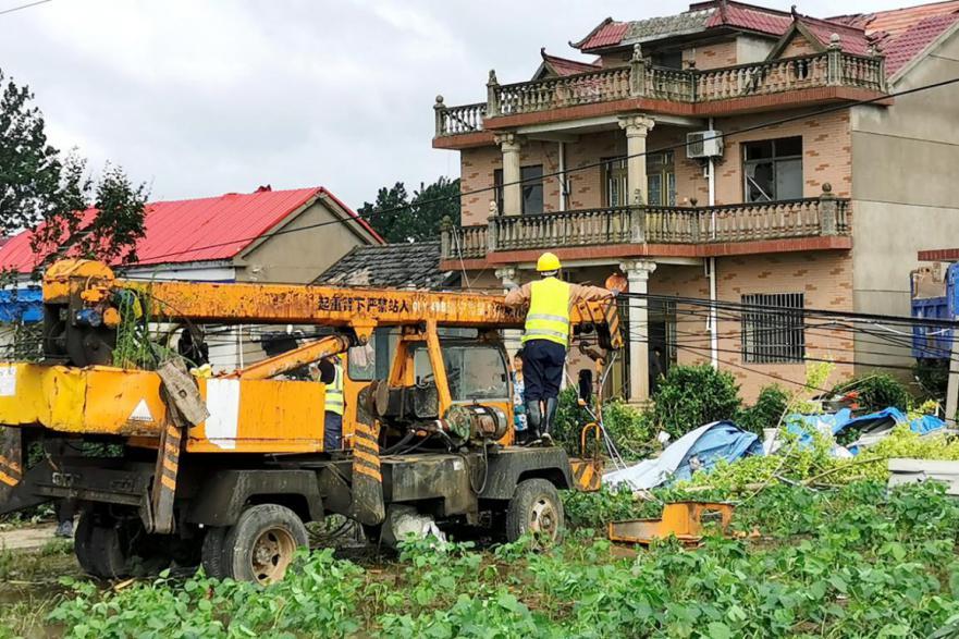 (移动抢修人员利用吊车清理受损杆路。)