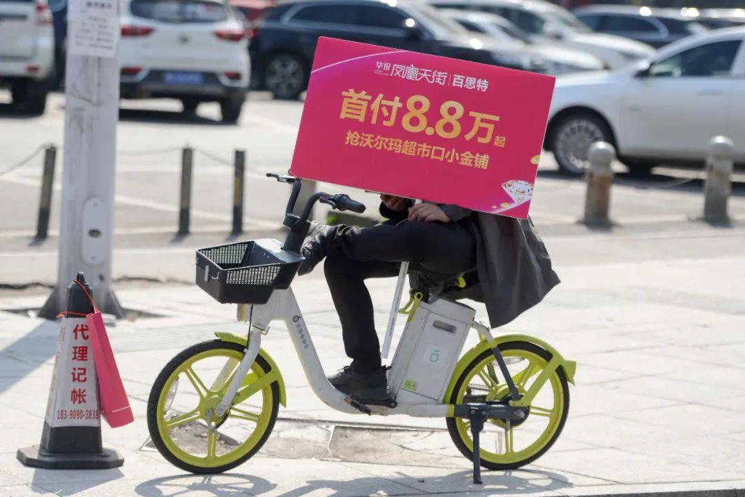 ▲ 长沙街头一位销售人员坐在共享单车上展示房地产广告。图 / 视觉中国