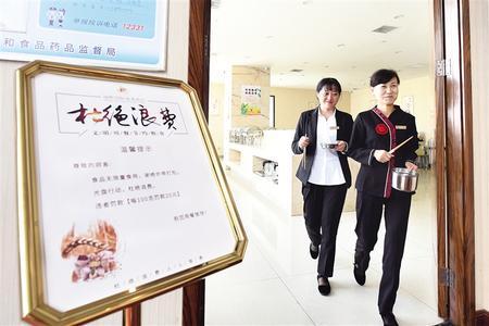 """新区瑞岭国际商务酒店就餐区,""""杜绝浪费""""提示牌摆放在门口显眼位置。记者 丁凯 摄"""