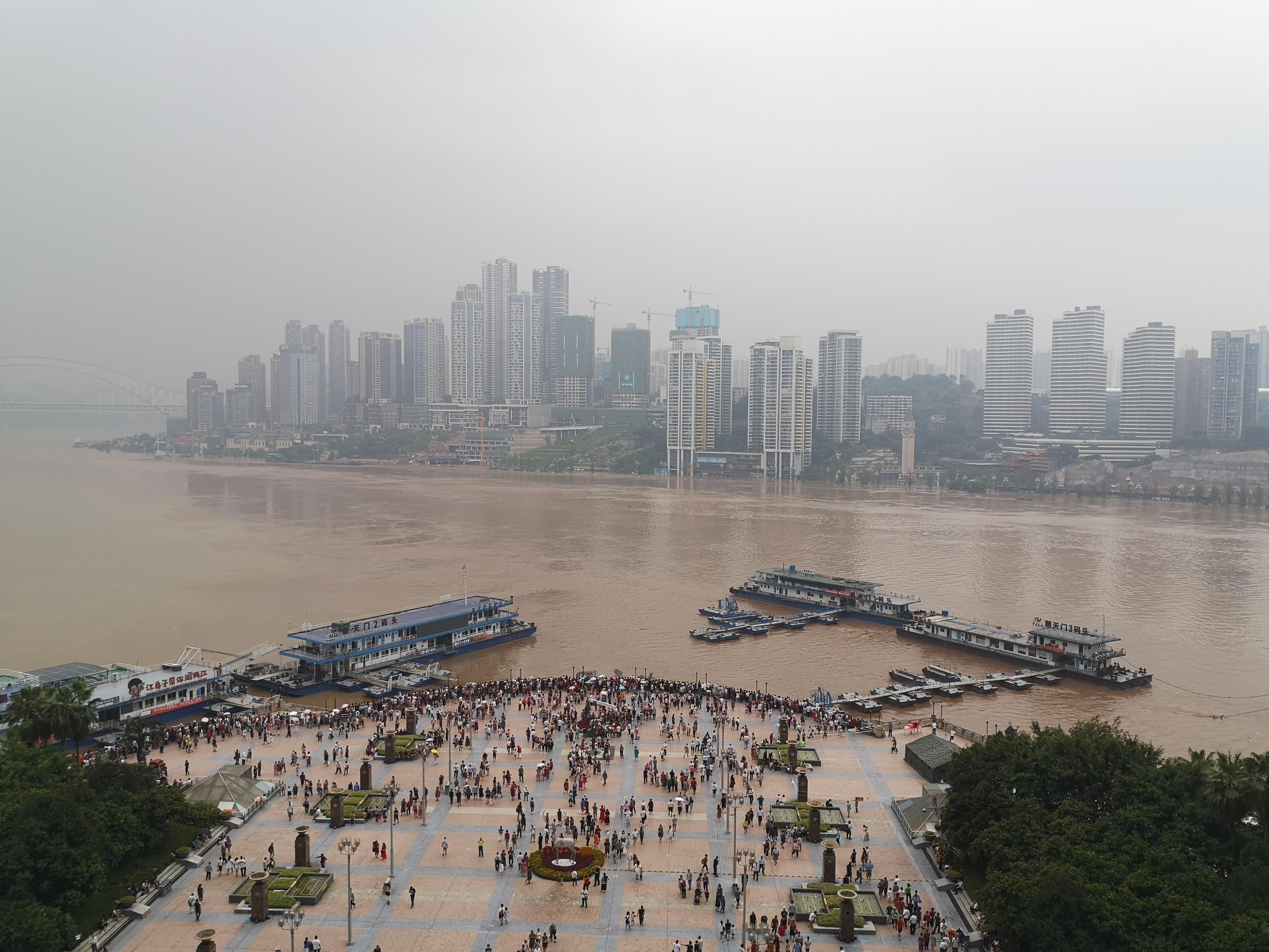 8月20日中午,重庆朝天门两江交汇处,不少市民在广场上看洪水。