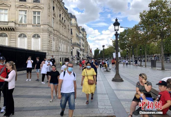 """当地时间8月14日,巴黎被法国官方列为新冠病毒传播""""高风险地区""""。图为当天在巴黎香榭丽舍大街的民众,其中一些人仍未戴口罩。 中新社记者 李洋 摄"""