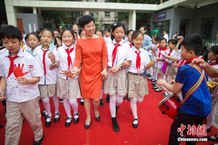 资料图:老师们牵着学生的手走过红地毯步入校园,并接受学生们的敬礼与祝福。 张云 摄