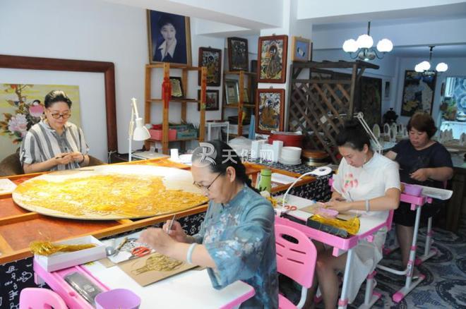 社区居民找到石梦,学习景泰蓝唐卡制作方法。