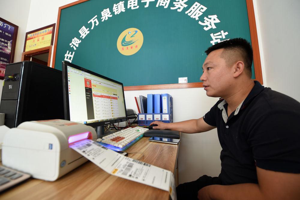 在庄浪县万全镇电子商务服务站,邵子斌在打印苹果网店订单快递单(9月3日摄)。新华社记者 范培珅 摄