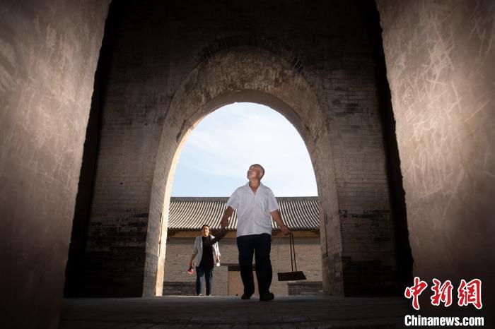 47岁的闫新安提着簸箕、扫帚,又一次走进寺庙大殿背后的麓台塔,开始逐层打扫。韦亮 摄