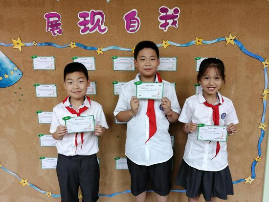 """三名小学生荣获""""小小管理员""""称号。费晓旭摄"""