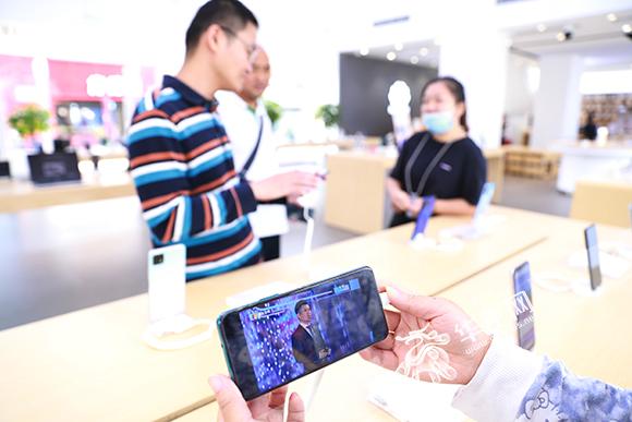 沙坪坝区熙街华为手机体验店,一位顾客正在用手机收看智博会直播。谢鹏 摄