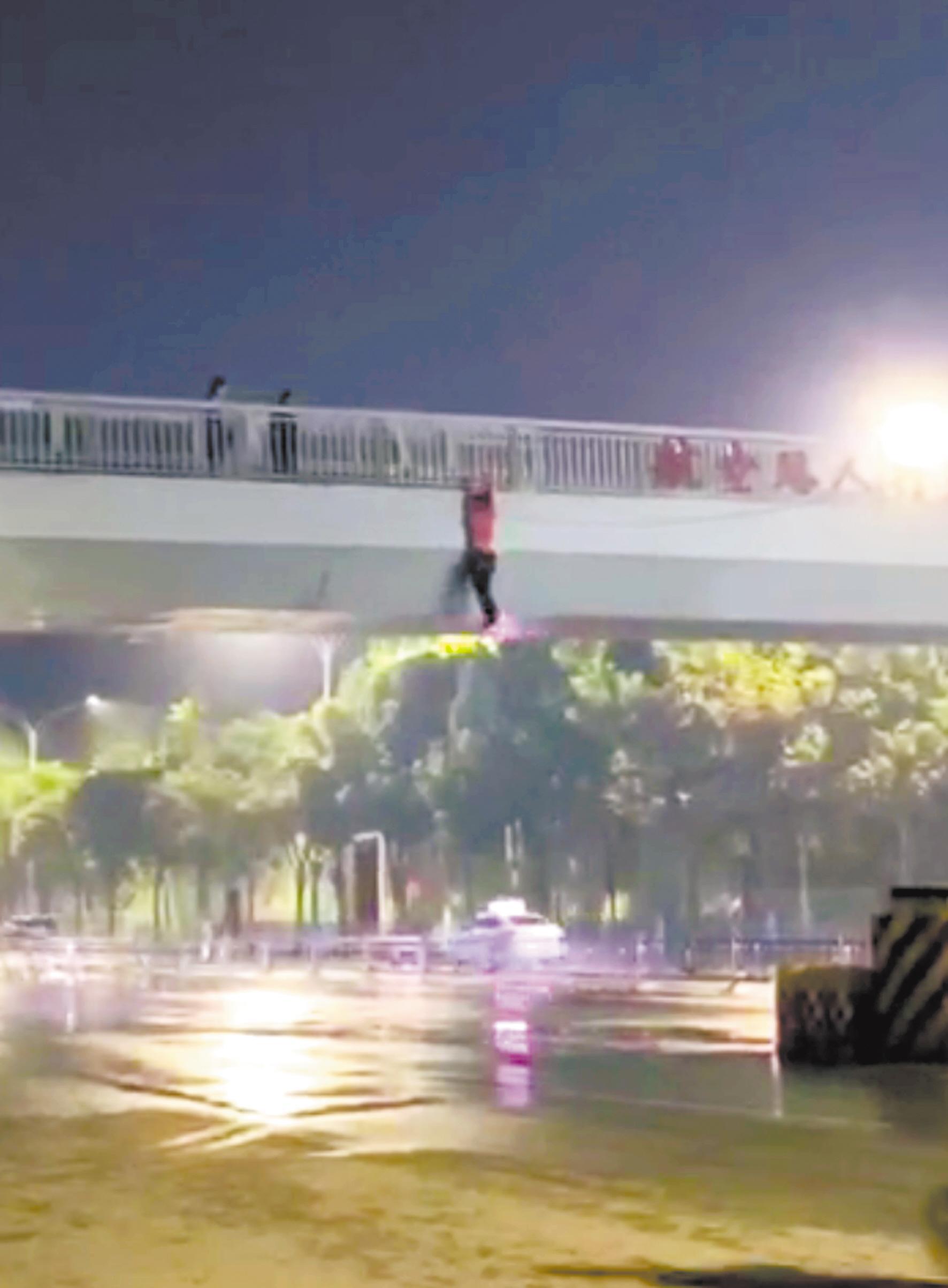 男子悬空在天桥外 (视频截图)