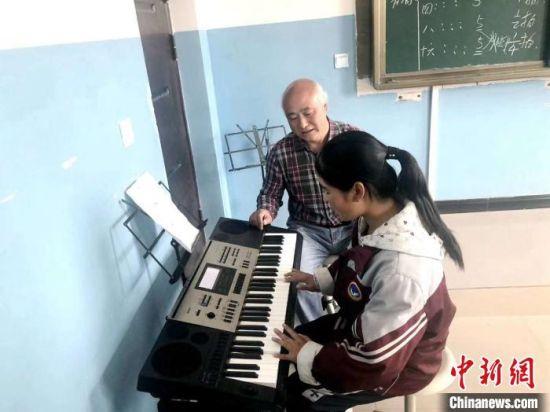 图为赵兴洲教学生弹电子琴。受访者提供
