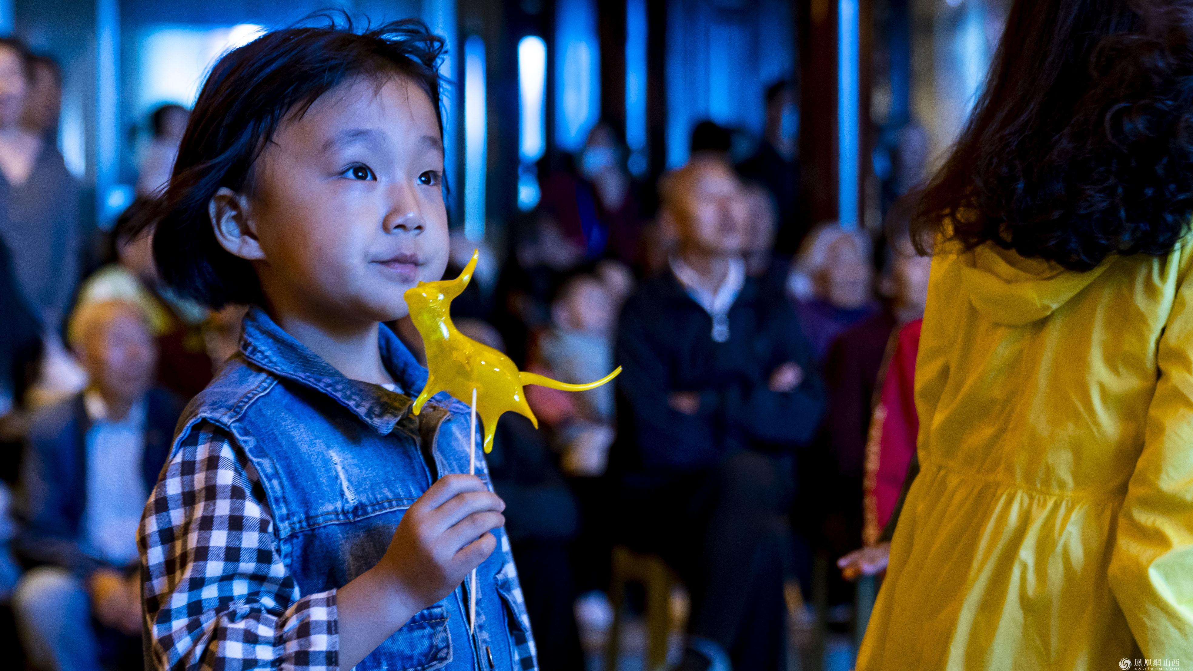 图为观众观看吹糖人表演。卢鹏宇 摄