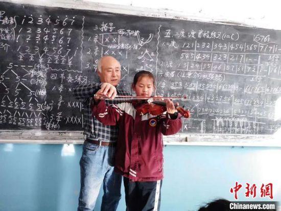 图为赵兴洲教学生拉小提琴。受访者提供
