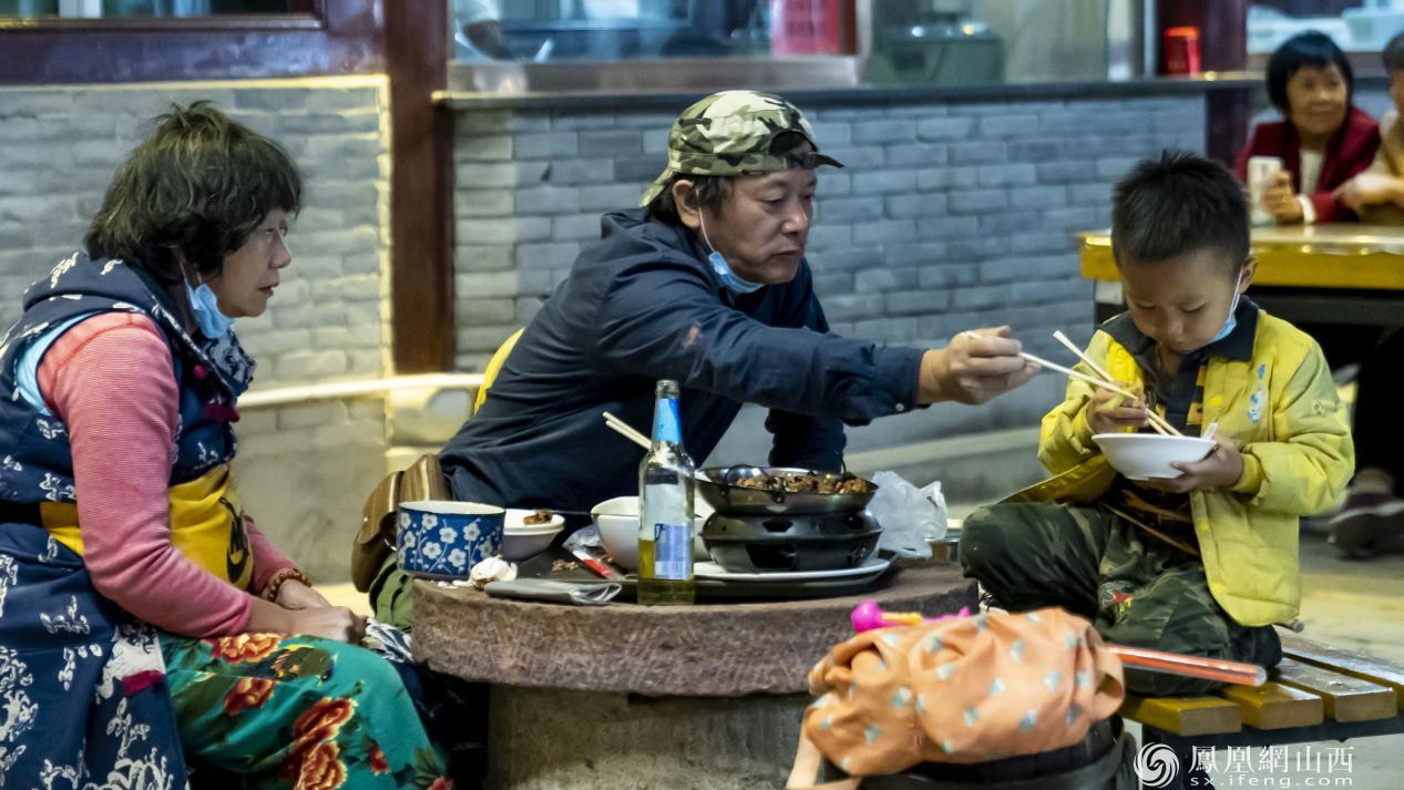 图为游客品尝夜市特色小吃。卢鹏宇 摄