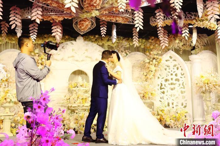图为婚庆公司摄像人员正在拍摄婚礼仪式上的一对新人。