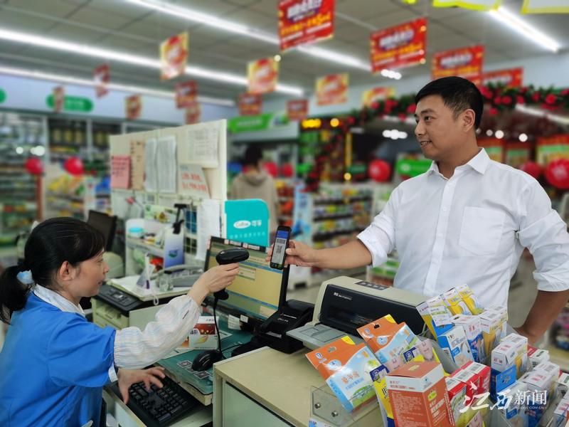 ▲抚州市民出示医保电子凭证购药。摄影|江西日报记者朱华