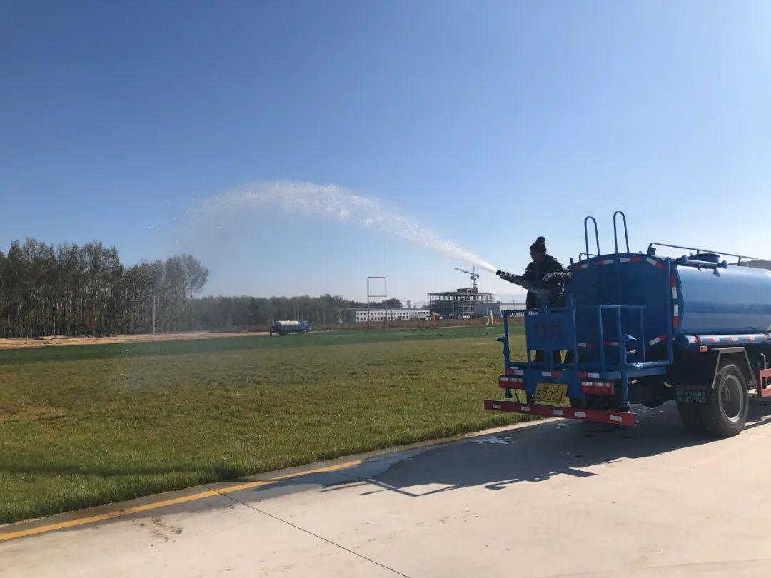 图为工作人员对比赛场地进行洒水保养。