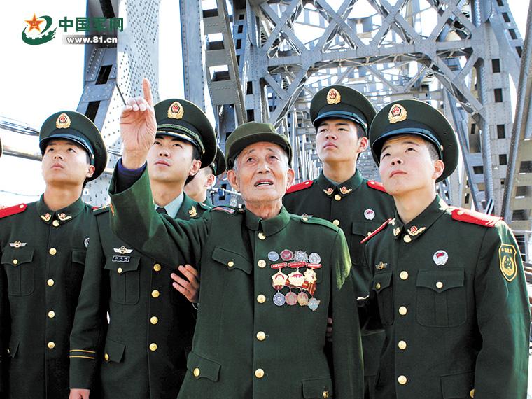 孙景坤(左三)为官兵讲述志愿军的战斗故事。吴 琼摄