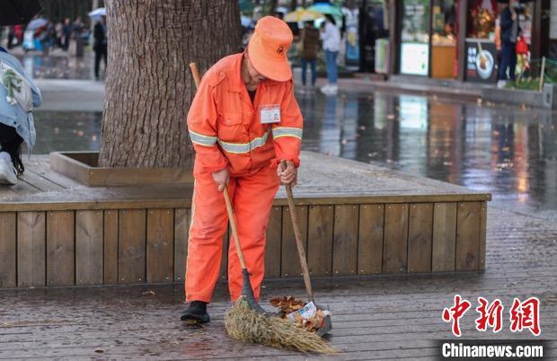 杭州西湖边清扫落叶的环卫工人。 汪旭莹 摄