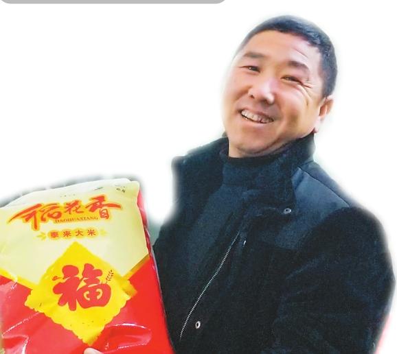 拿着刚刚生产出的新米,大米加工厂老板喜笑颜开。