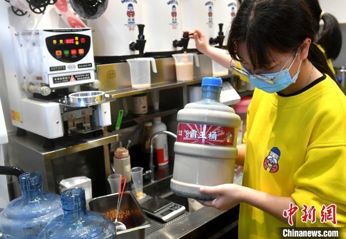 """一奶茶店工作人员正在制作5升""""霸王桶""""奶茶。 吕明 摄"""