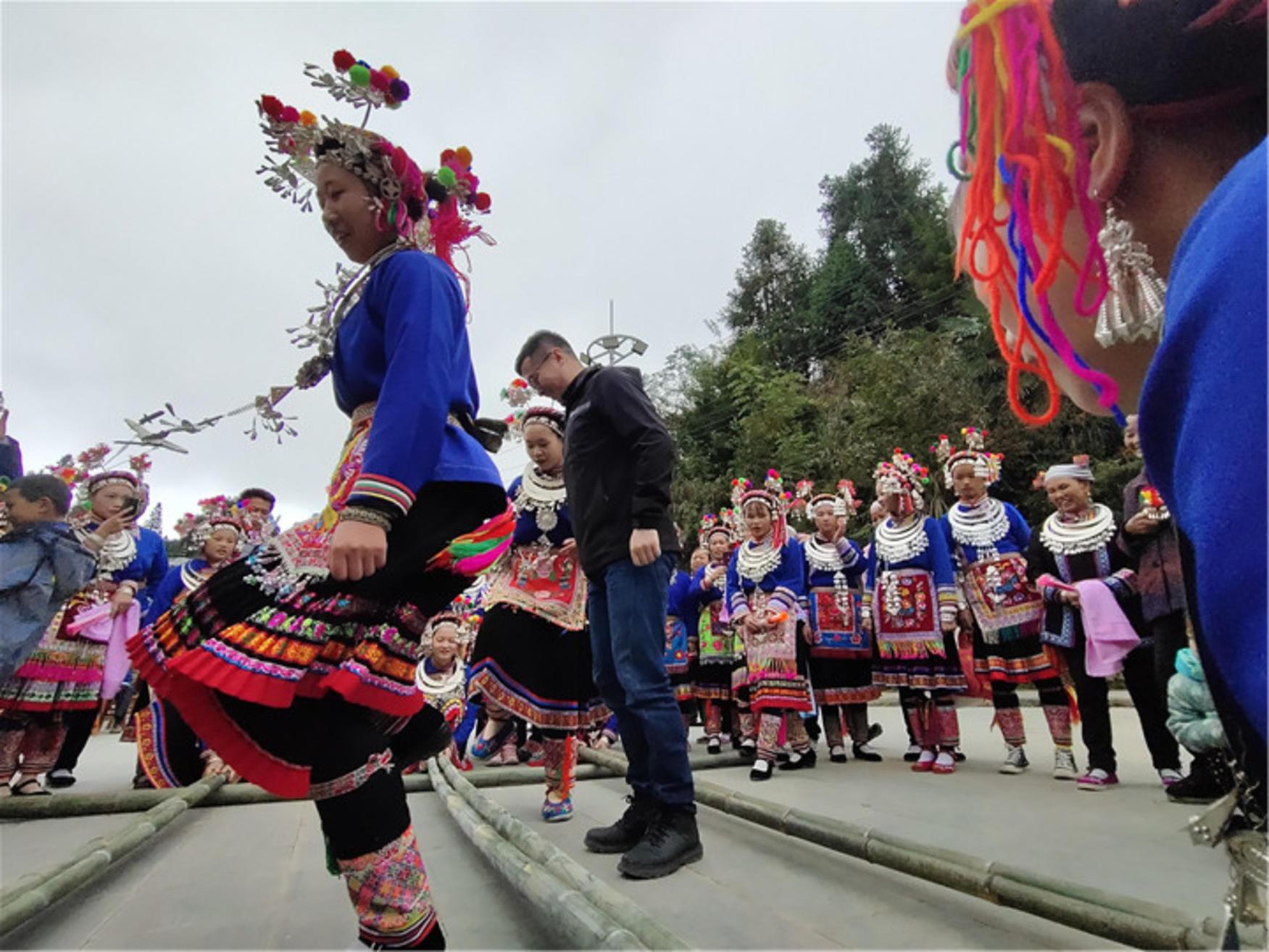 侗族阿妹和游客在跳竹竿舞