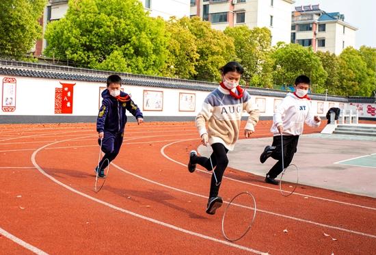 """4月22日,江苏省海安高新区田庄小学的学生们正在体育课上快乐地玩着传统游戏""""推铁环""""。人民视觉供图"""