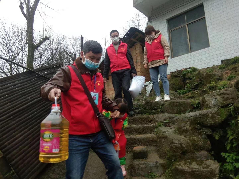 疫情期间,罗永华带着妻子和女儿及好人协会成员为贫苦户送去粮食和防疫物资