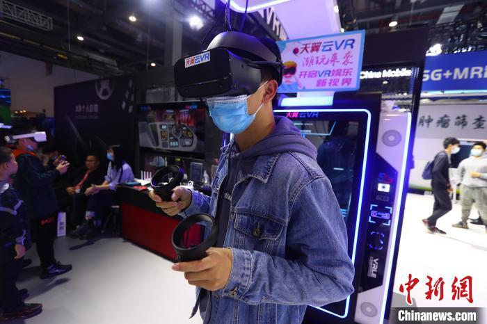 """同期举行的""""2020VR/AR产品和应用展览会""""上,参观者在体验VR设备。 刘占昆 摄"""