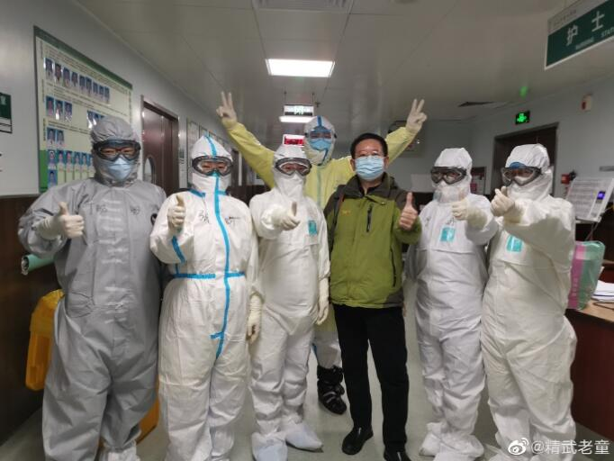 """53岁的童明俊(右三)不幸感染新冠肺炎,但这位武汉人却把微博名字改成""""幸运的老童""""。他在病房里用手机敲字、拍照,记录给他带来幸运的人——河北支援湖北医疗队中的十几位护士姑娘。出院前,他与河北支援湖北医疗队队员合影。 童明俊供图"""