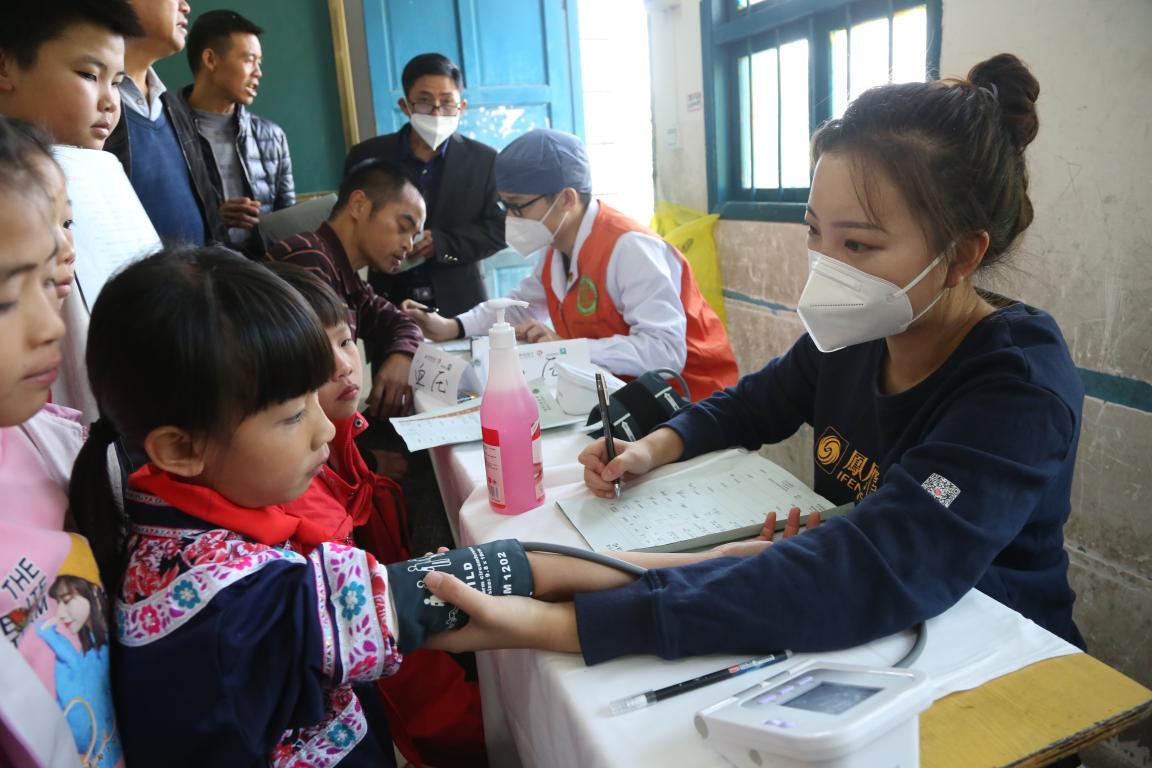 志愿者在给孩子们测量血压