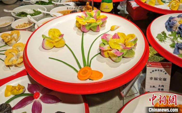 """图为""""七彩饺子"""",配以胡萝卜和小葱等摆盘,形成花朵的样子。 闫姣 摄"""