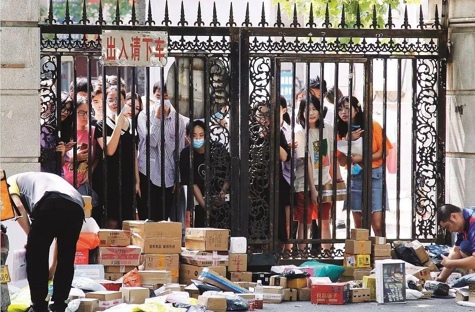 9月12日,河南郑州市一所大学校门前,学生们隔着栅栏门领取快递包裹。图/视觉中国