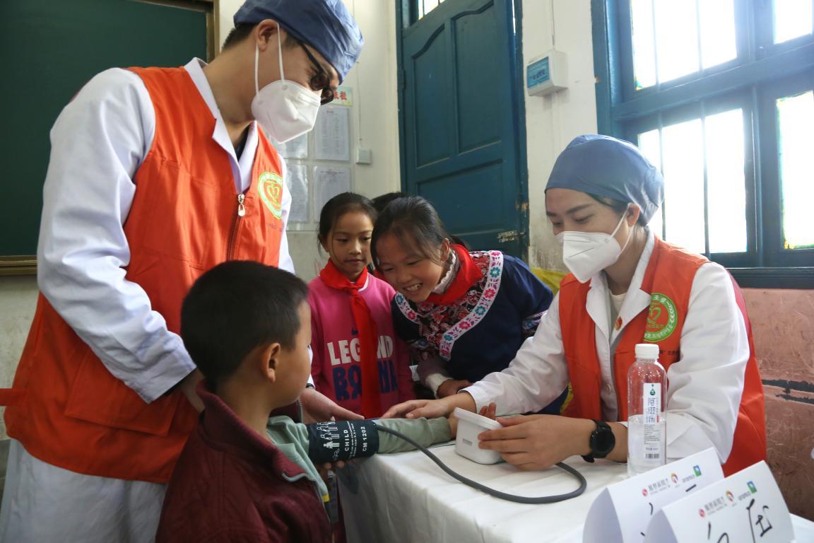 内科的医疗志愿者正在为孩子测量血压