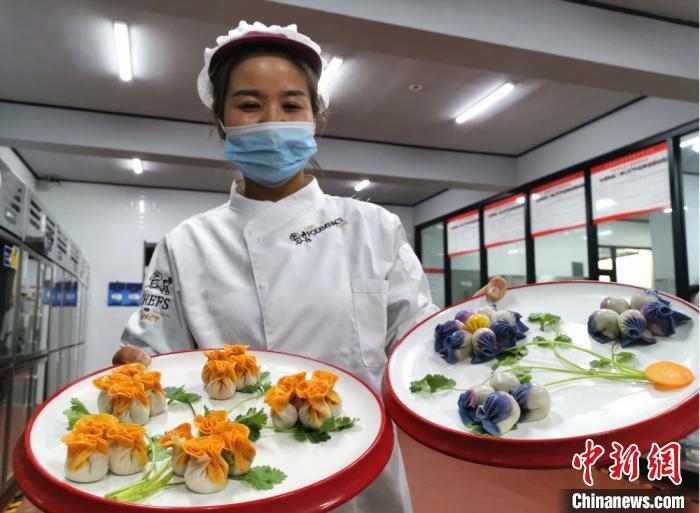 图为金昌市一宾馆的厨娘徐换弟介绍创意七彩饺子宴。 闫姣 摄