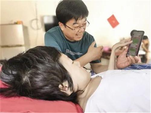 躺在自家护理床上的董萱萱向扶贫干部李松涛介绍网店经营情况