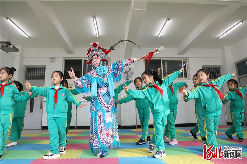 2020年11月19日,河北省唐山市京剧艺术团演员在唐山市丰润区迎宾路小学为学生示范戏曲动作。