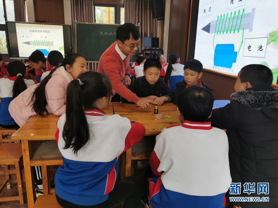 在重庆市石柱土家族自治县中益乡小学,唐大鹏(中)给孩子们上科学课(10月20日摄)。