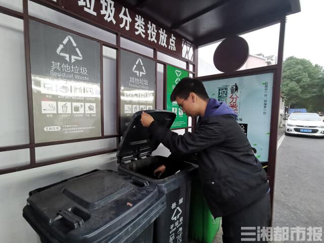 (11月20日,市民正在垃圾分类投放点投放垃圾。杨洁规 摄)