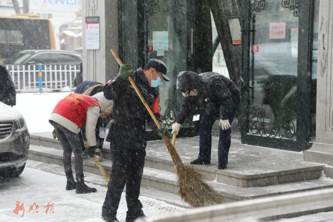 医大地铁站工作人员及时清理门前积雪。哈尔滨日报手机记者 乐晨 摄