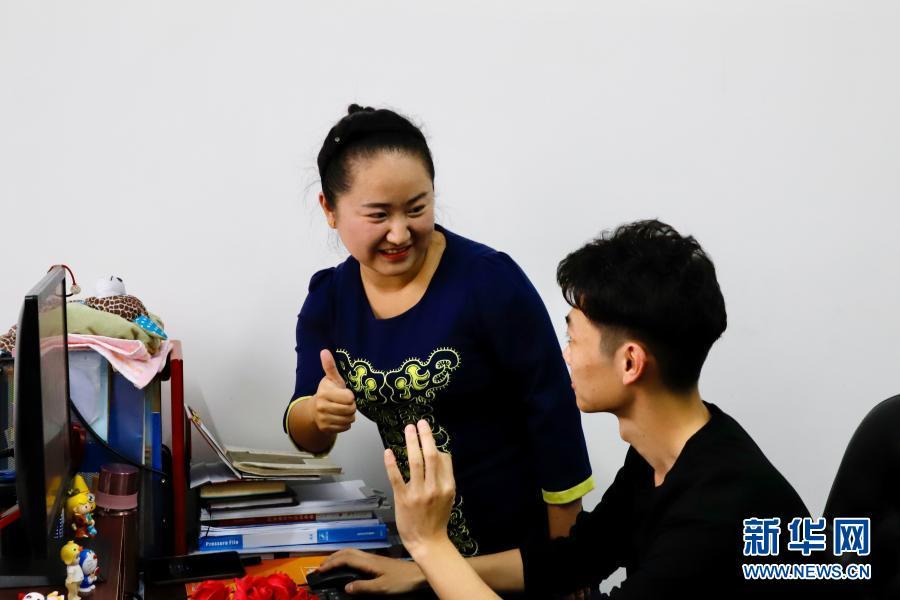 11月18日,在黑龙江绥化学院,李泽卉(左)用手语和学生交流。